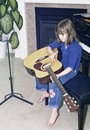Little girl sits on piano bench to practice guitar Stock Images