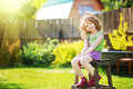 Little girl sits on a wooden chair in the yard of a country house. Royalty Free Stock Photo