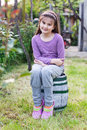 Little girl sitting on barrel in garden adorable a small a or park Stock Images