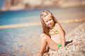 Little girl sitting on the beach near the sea six year old blonde in a bathing suit with her hair water Stock Image