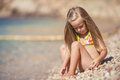 Little girl sitting on the beach near the sea six year old blonde in a bathing suit with her hair water Stock Photo