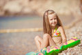 Little girl sitting on the beach near the sea six year old blonde in a bathing suit with her hair water Royalty Free Stock Photography
