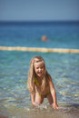 Little girl sitting on the beach near the sea six year old blonde in a bathing suit with her hair water Royalty Free Stock Photo
