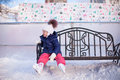 Little girl sitting on a bench in the skating rink Royalty Free Stock Photo