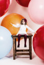 Little girl sitting on the big chair background of large multi colored balloons Stock Photo