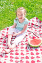 Little girl sitting on a blanket in the park Royalty Free Stock Images
