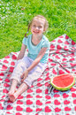 Little girl sitting on a blanket in the park Stock Photo