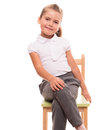 Little girl sitting on a chair and smiling it s comfortable to posing while Stock Photo