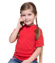 Little girl sitting on a chair and speaking by smartphone Stock Photography
