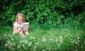 Little girl sitting with computer outdoors Royalty Free Stock Photo