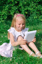 Little girl sitting with computer outdoors Stock Photos