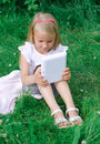 Little girl sitting with computer outdoors Royalty Free Stock Photos