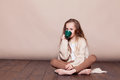 stock image of  Little girl sitting on the floor and drinking tea