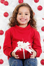 Little girl sitting in front of a christmas tree Royalty Free Stock Photos