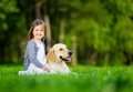 Little girl sitting on the grass with labrador retriever in summer park Stock Photo