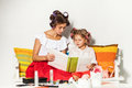 Little girl sitting with her mother and looking at a photo album Royalty Free Stock Photo