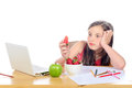 A little girl sitting at his desk eating a strawberry Royalty Free Stock Photo