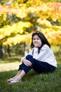 Little girl sitting on lawn in autumn Royalty Free Stock Image