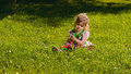 Little girl sitting on the lawn lit by sun Royalty Free Stock Photo