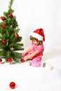 Little girl sitting near Christmas tree  Royalty Free Stock Photography