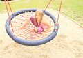 Little girl sitting on a net swing hairy and swinging made from ropes kids playground Royalty Free Stock Photos