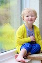 Little girl sitting next window on rainy day cute child blonde curly toddler in colorful casual outfit indoors a autumn looking Royalty Free Stock Photos