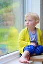 Little girl sitting next window on rainy day cute child blonde curly toddler in colorful casual outfit indoors a autumn looking Stock Photo