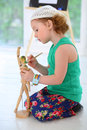 Little girl sitting and paints wooden man the on the floor Royalty Free Stock Image
