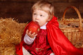 Little girl is sitting on pile of straw eating apple little red riding hood Stock Image