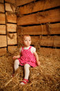 Little girl is sitting on pile of straw in hayloft Stock Photos