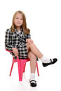 Little girl sitting in pink chair with white background Stock Photography