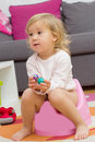 Little girl sitting on the potty at home Royalty Free Stock Photography