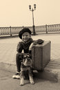 Little girl sitting on the road with a dog and suitcase Royalty Free Stock Images