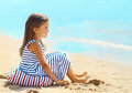 Little girl sitting on the sand beach near sea in summer Royalty Free Stock Photo