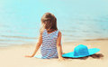 Little girl sitting on the sand beach with straw hat near sea Royalty Free Stock Photo