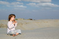 Little girl sitting on sand and play music pan pipe Stock Photos