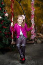 Little girl sitting on the swing happy near a christmas tree Royalty Free Stock Image