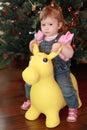 Little girl sitting on toy donkey Royalty Free Stock Photos