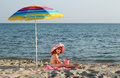 Little girl sitting under sunshade on beach happy Stock Photography