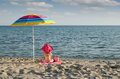 Little girl with sitting under sunshade on beach hat Royalty Free Stock Photos