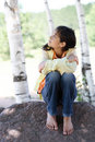 Little girl sitting under trees Royalty Free Stock Photo