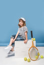 Little girl sitting on white boxes with tennis raquet and balls Royalty Free Stock Photo