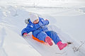 Little girl on a sled sliding on snow down hill in the in winter Royalty Free Stock Photo