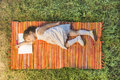 Little girl sleeping on the opened notebook lying down on the picnic blanket Royalty Free Stock Photo