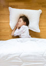 Little girl sleeping on wooden floor on white pillow Royalty Free Stock Photo