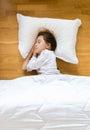 Little girl sleeping on wooden floor on white pillow Royalty Free Stock Photo