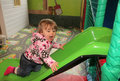 Little girl on a slide having fun in an indoor activity centre Royalty Free Stock Photo