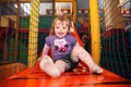 Little girl on a slide having fun in an indoor activity centre Stock Image