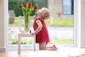 Little girl smelling beautiful tulips pretty blonde toddler playing with standing on the tiles floor next to a big window with Stock Image