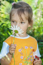 Little girl smells chamomile in yellow dress on green meadow Stock Image